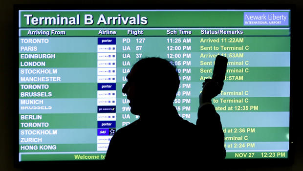 A person points to a screen displaying an airplane travel list while he talks on a phone at Newark Liberty International Airport as travelers get a head start on Thanksgiving Day travel Nov. 27, 2013, in Newark, N.J.