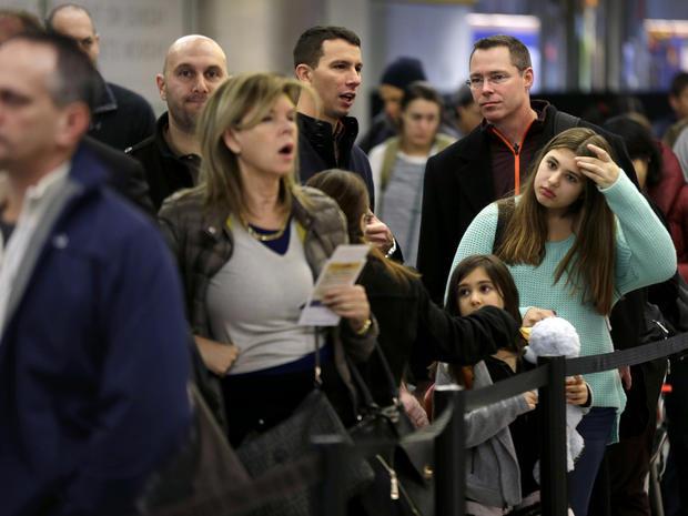 旅行者排队等候在2013年11月26日在纽约拉瓜迪亚机场登机。