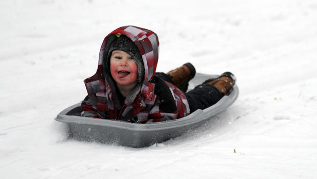 Matthew Mattei, 2, sleds backwards in Grosse Pointe Farms, Mich., Jan. 1, 2014. Michigan residents are facing a white and chilly New Year's Day, with snow falling in many parts of the Lower Peninsula and temperatures hovering around zero in parts of the U