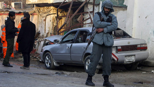 An Afghan policeman stands near a damaged car outside a Lebanese restaurant, the site of a suicide attack, in Kabul Jan. 18, 2014.