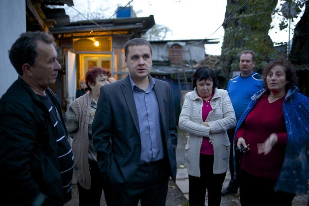 Igor Zarytovsky, center, and his father Vladimir, left, gather  with their neighbors in the yard of the railroad house in the village of Vesyoloye outside Sochi, Russia.