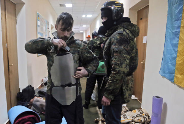 A protester puts homemade steel plates on the chest as he prepares to leave the Agriculture Ministry in Kiev.