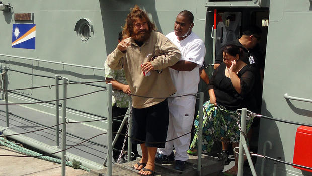 """A castaway from Mexico who identified himself as Jose Salvador Alvarenga steps off the """"Lomor"""" Sea Patrol vessel in Majuro, Marshall Islands, with the help of a nurse"""
