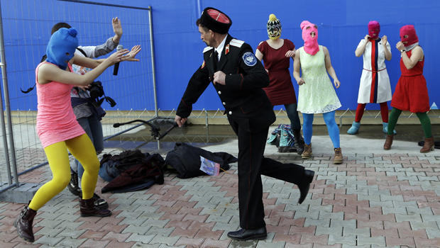 A Cossack militiaman attacks Nadezhda Tolokonnikova and a photographer as she and fellow members of the punk group Pussy Riot, including Maria Alekhina, center, in the pink balaclava, stage a protest performance in Sochi, Russia, Feb. 19, 2014.