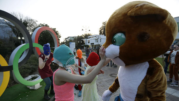 Pussy Riot member Nadezhda Tolokonnikova in the aqua balaclava, left, interacts with a person dressed as one of the Olympic mascots while the group performs next to the Olympic rings in Sochi, Russia, Feb. 19, 2014.