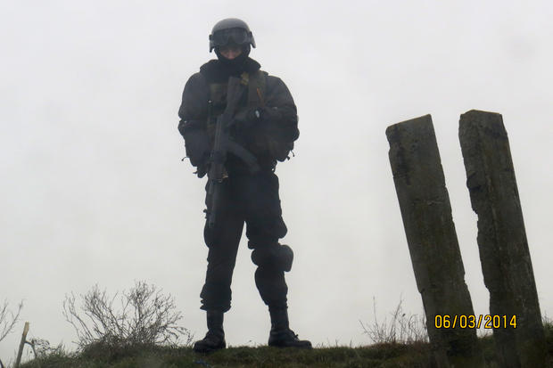 An unidentified armed man looks down from a hillop at a checkpoint on the Crimean border