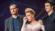 Dancer Adrianne Haslet-Davis, center, wipes away a tear while standing on stage with MIT professor Hugh Herr, left, and dancer Christian Lightner at the 2014 TED Conference March 19, 2014, in Vancouver, British Columbia, in this picture provided by TED 20