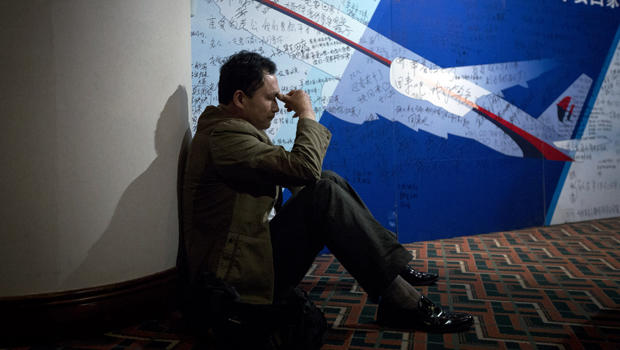 A man, one of the relatives of Chinese passengers onboard Malaysia Airlines Flight 370, rests near a board covered with written wishes at a hotel in Beijing March 29, 2014.