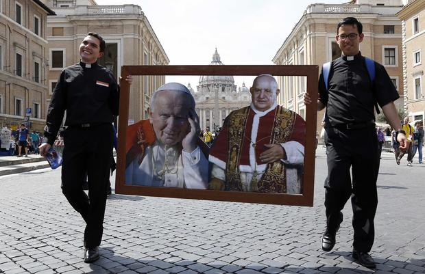 Two priest walk carrying pictures of Pope John Paul II (L) and Pope John XXIII in front of St. Peter's square