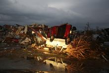 A flipped pickup truck is reflected in water after a tornado destroyed the town of Mayflower, Arkansas