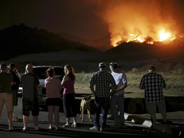 2014年5月14日,居民在加利福尼亚州圣马科斯观看快速移动的野火方法。