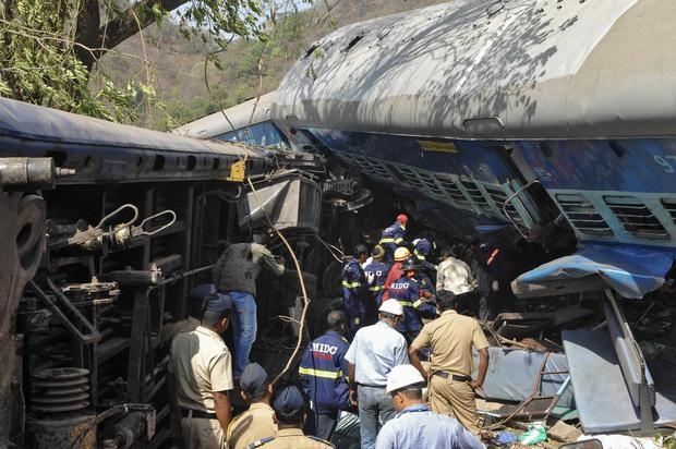 Rescuers search for survivors from the debris of a passenger train after it derailed near Nidi village, south of Mumbai, in the western Indian state of Maharashtra