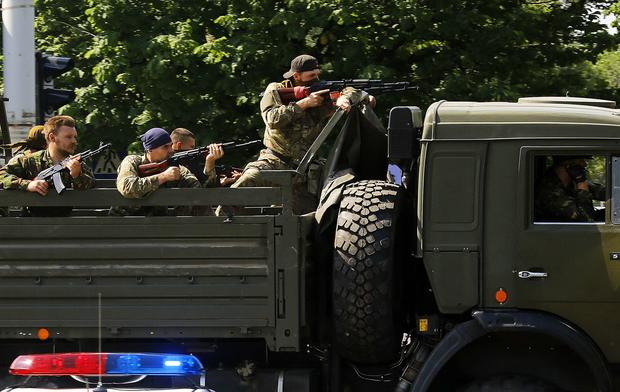 A military truck with armed pro-Russian militants drives through a police check-point toward the airport of the eastern city of Donetsk