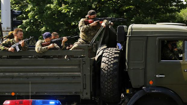 A military truck with armed pro-Russian militants drives through a police check-point towards the airport of the eastern Ukrainian city of Donetsk