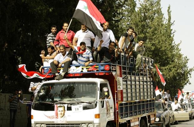 Syrian refugees ride on a truck adorned with pictures of Syrian President Bashar Assad near the southern city of Sidon, May 28, 2014, on the way to the Syrian embassy to cast their ballots in the Syrian presidential elections