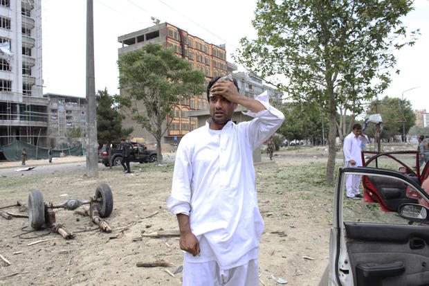 man reacts at the site of a suicide attack that struck the convoy of presidential candidate Abdullah Abdullah