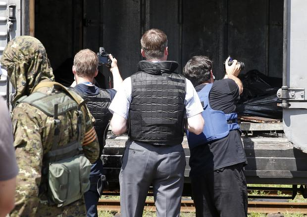 Monitors from the OSCE inspect a refrigerator wagon holding bodies of passengers from Malaysia Airlines flight 17