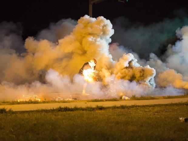 2014年8月13日,一名抗议者在密苏里州弗格森与警察发生冲突时投掷了一枚烟雾弹。