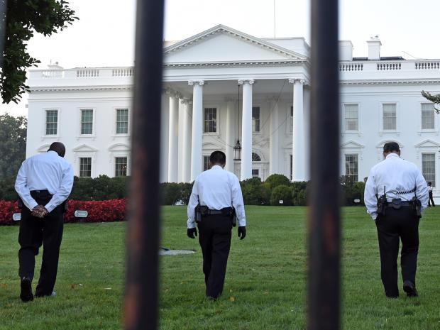 穿着制服的特勤人员于2014年9月20日在华盛顿白宫北侧的草坪上行走。