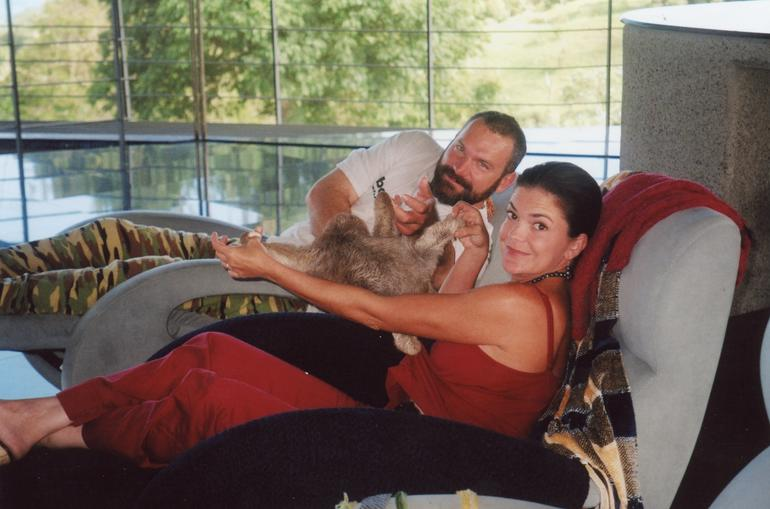 Ann and John Bender pose with a pet sloth