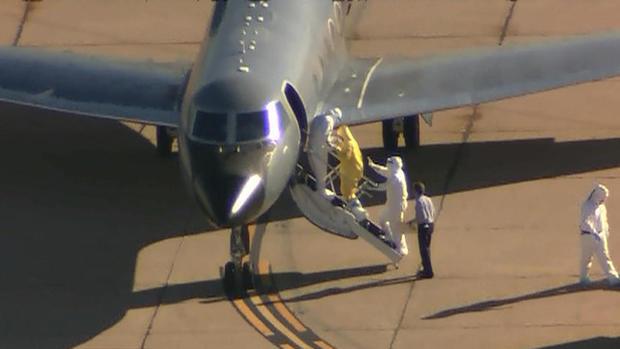 穿着黄色西装的埃博拉病人Amber Vinson正在登机,将她从达拉斯带到亚特兰大埃默里大学医院