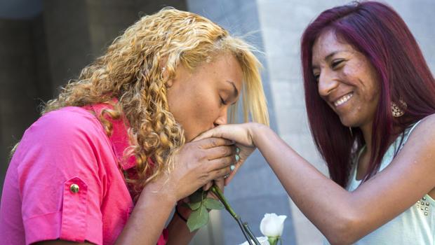 在2014年10月17日凤凰城马里科帕县高级官员办公室外的婚礼仪式结束后,Shaday Escalera离开,亲吻了她的搭档Leilanny Salcido的手。