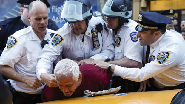 2015年4月29日,纽约警察局官员在纽约曼哈顿区游行期间拘留一名抗议者,呼吁社会,经济和种族正义。