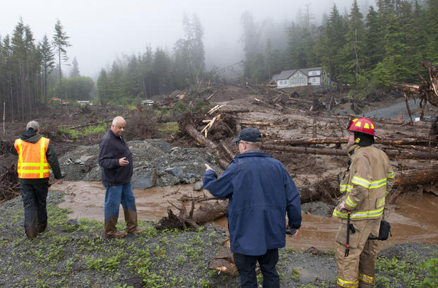 左起,城市工程师Dan Tadic,消防队长Dave Miller,搜索和救援队长Lance Ewers和消防员Rob Janik看看2015年8月18日在阿拉斯加州Sitka发生的山体滑坡造成的破坏。