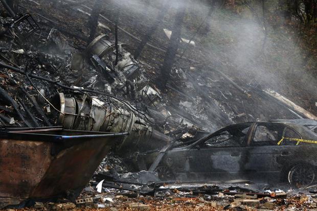 当局称,一架小型公务机在2015年11月10日在俄亥俄州阿克伦城的一座公寓大楼坠毁,烧焦的汽车和飞机碎片闷烧。