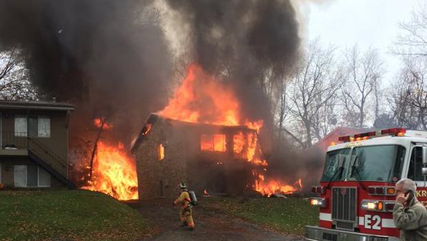 2015年11月10日,一架小型公务机坠毁在俄亥俄州阿克伦城的一栋公寓楼后,工作人员开始工作。