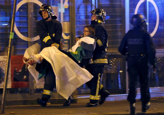 French fire brigade members aid an injured individual near the Bataclan concert hall following fatal shootings in Paris, France, Nov. 13, 2015.