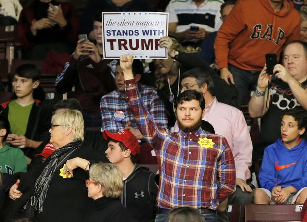 A protester, center, stands as Republican presidential candidate Donald Trump speaks during a campaign event in Rock Hill, South Carolina, Jan. 8, 2016.