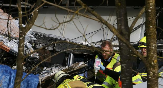 Members of emergency services hold an infusion bottle at the site of the two crashed trains near Bad Aibling in southwestern Germany