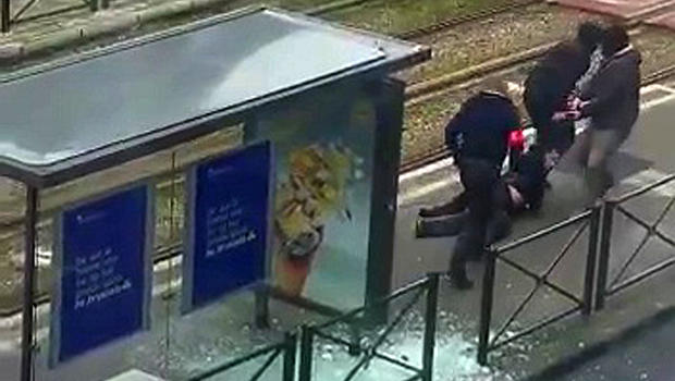 Belgian police drag a suspect along a tramway platform after the suspect was shot in this still image taken from amateur video in the Brussels borough of Schaerbeek March 25, 2016, three days after the bombings in Brussels, Belgium.