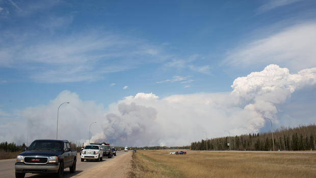 Vehicles drive away from Fort McMurray as winds pick up and smoke begins to darken just south of the oil sands city in Fort McMurray, Alberta, Canada on May 4, 2016