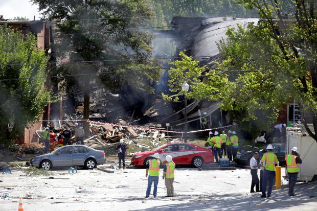 2016年8月11日,马里兰州Silver Spring的一场致命爆炸中,消防员透过四层楼房的碎片进行了查看。