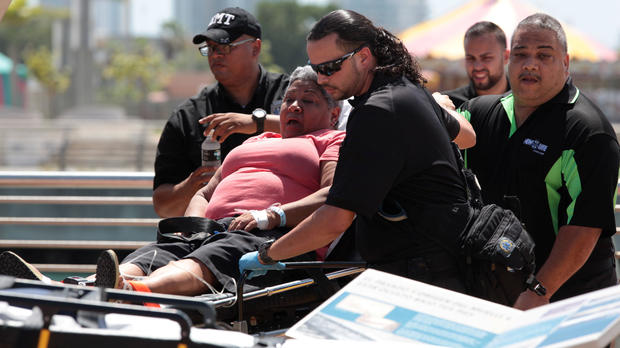 A passenger from the Caribbean Fantasy is carried on a stretcher after being rescued from the ship that was burning about two miles off of San Juan, Puerto Rico, Aug. 17, 2016.