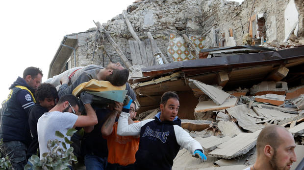 A man is carried away after having been rescued alive from the ruins following an earthquake in Amatrice, Italy, Aug. 24, 2016.