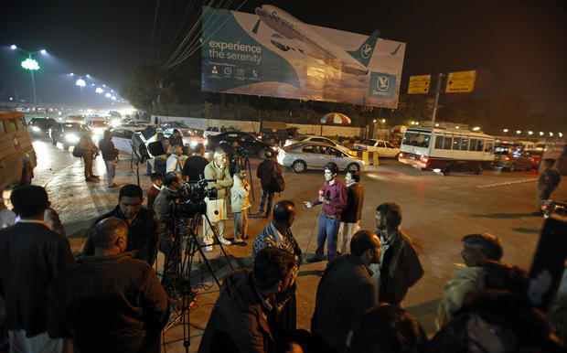 Pakistani media and residents gather at Benazir Bhutto International Airport following a report that a passenger plane from Chitral had crashed near a village near the town of Havelian, in Islamabad, Pakistan, Dec. 7, 2016.