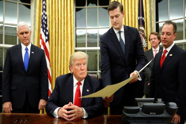白宫工作人员秘书Rob Porter,右三,给特朗普总统,副总统Mike Pence和参谋长Reince Priebus,右边,文件确认James Mattis为他的国防部长,特朗普先生首次在椭圆形办公室签字在华盛顿2017年1月20日。
