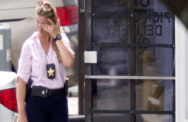 2017年6月5日,一名执法官员在佛罗里达州奥兰多的射击犯罪现场的入口处擦了擦眼睛。