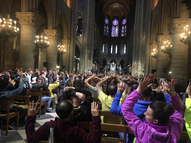 Visitors to Notre Dame Cathedral raise their hands during a security operation after a man attacked police officers with a hammer outside the cathedral in Paris on June 6, 2017.
