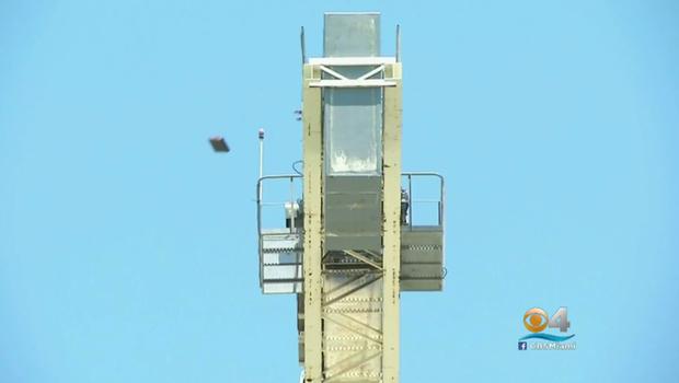 Police: Naked man climbs 300-foot crane, drops heavy ...