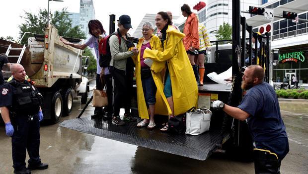 在飓风哈维淹没德克萨斯海湾沿岸的雨水引起大面积洪水之后,撤离人员从乔治布朗会议中心的一辆开放式卡车的后面卸下