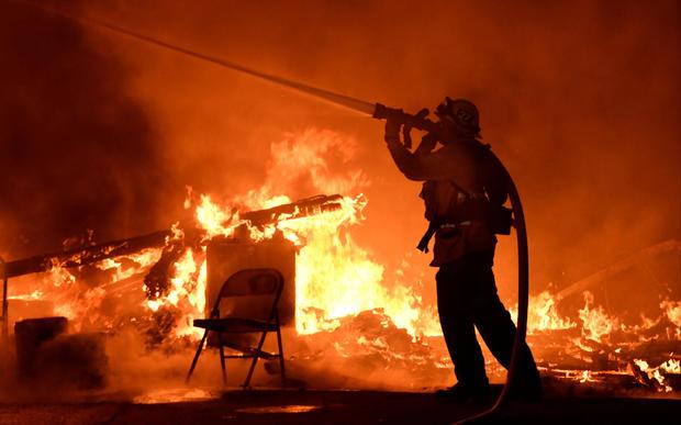消防队员在2017年12月4日在加利福尼亚州圣保拉的Santa Ana风力驱动刷火中与火焰战斗。