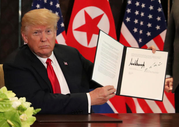 Donald Trump signing U.S.-North Korea summit