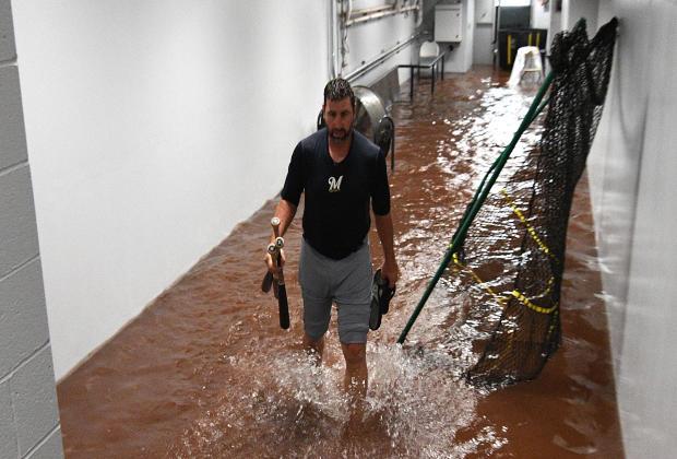 密尔沃基酿酒人队第55号的马库斯·哈内尔于2018年6月20日在宾夕法尼亚州匹兹堡与PNC公园的匹兹堡海盗队进行了一场比赛中的雨水延迟,穿过防空洞外的一条被水淹没的走廊。
