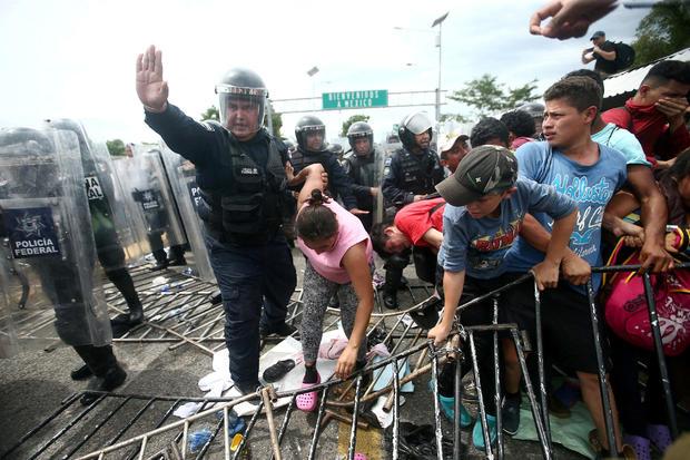 一名警察帮助一名洪都拉斯移民,一名试图前往美国的大篷车的一部分,她在Ciudad Hidalgo掠过边境检查站进入墨西哥