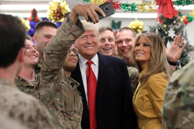 在伊拉克Al Asad空军基地的暗访期间,美国总统特朗普和第一夫人在餐饮场所迎接军事人员