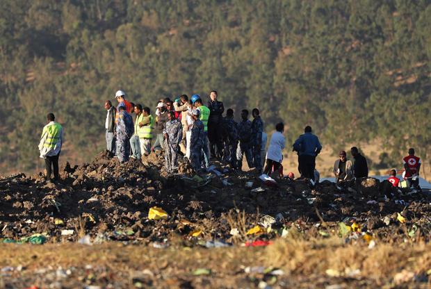 搜索和救援任务的成员在Bishoftu附近的埃塞俄比亚航空公司ET 302飞机失事现场寻找乘客的尸体